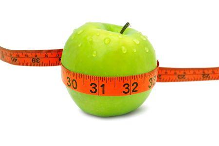 Green apple with red measuring tape. 版權商用圖片
