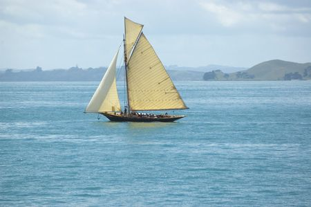 maneuvering: Vintage leisure sail boat with tourists on vacation cruising around islands along sea shore