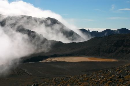 Red volcano crater lake and a cloud sitting on it as fog. Tongariro crossing, New Zealand photo