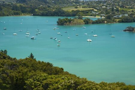 Idyllic view on yachts and boats standing in blue lagoon, forest, village and winery.