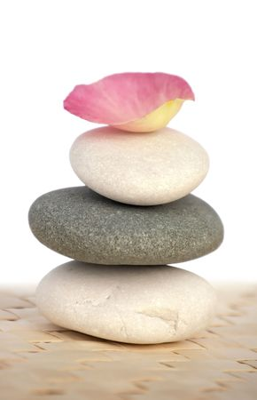 Rose petal on pyramid of pebbles. Spa series. Isolated over white. photo