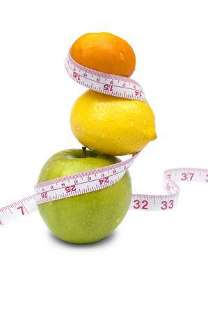La pérdida de peso y una dieta saludable concepto. Apple, limón y mandarina con cinta de medir. Aislado en blanco.
