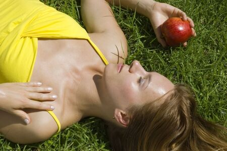 Young tanned woman resting on the grass with red apple Stock Photo - 2656735