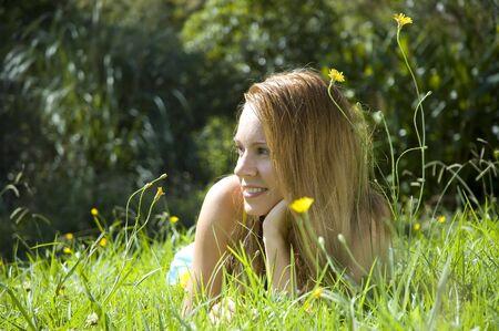 Happy beautiful young woman in green summer field 版權商用圖片