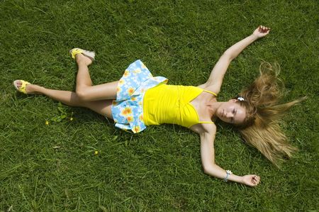 Attractive young woman in mini skirt laying on grass. Summer concept.