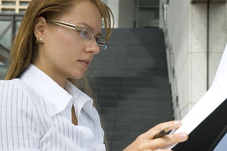 Attractive Blonde business woman reading document outside office