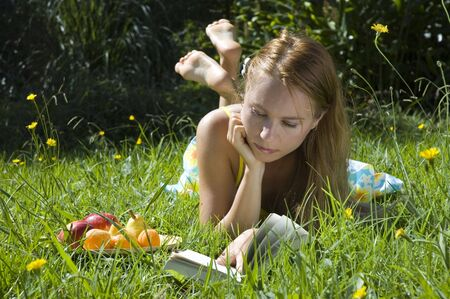 Young blonde woman reading a book on the grass with plate of fruits on summer holidays photo