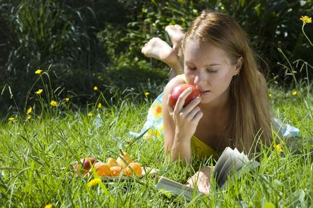 Beautiful young woman eating apple and reading book on grass