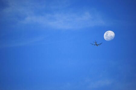 Plane and moon against blue sky.