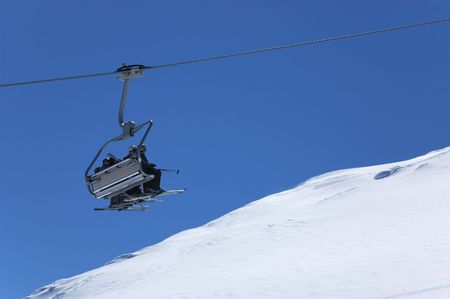 Chair lift with skiers going up at ski resort. Blue sky and white snow  on background
