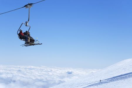 Chair lift with skiers at ski resort above the clouds. Snowboarder on the slope.