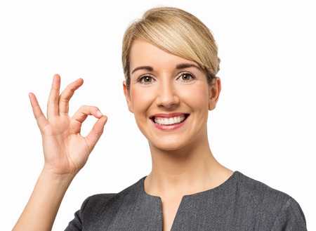 Portrait of smiling young businesswoman gesturing okay over white background  Horizontal shot  Stock Photo