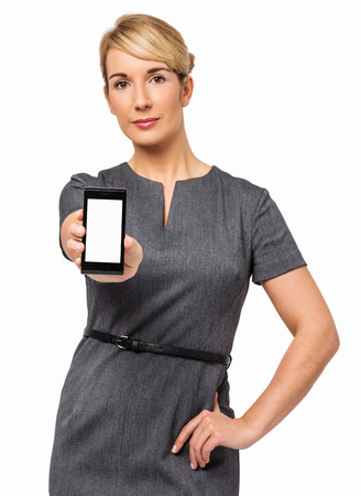Portrait of confident businesswoman showing smart phone against white background  Vertical shot  photo