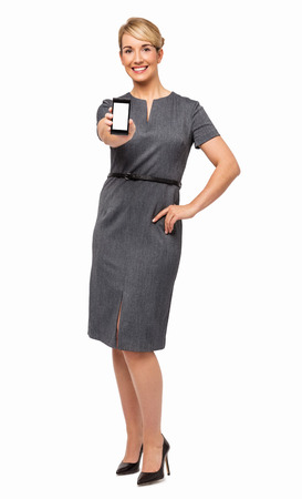 Portrait of confident businesswoman showing smart phone isolated over white background  Vertical shot  photo