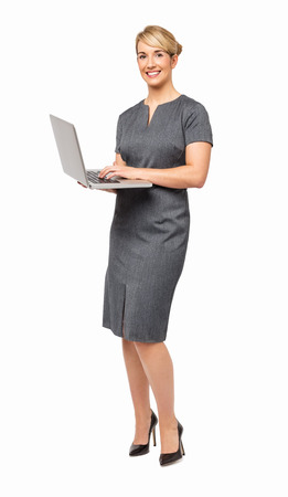 Full length portrait of happy businesswoman using laptop against white background  Vertical shot