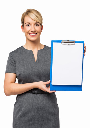 Portrait of happy businesswoman showing blank paper on clipboard against white background  Vertical shot  photo