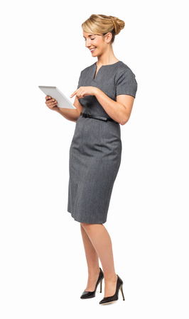 Full length of young businesswoman using digital tablet against white background. Vertical shot.