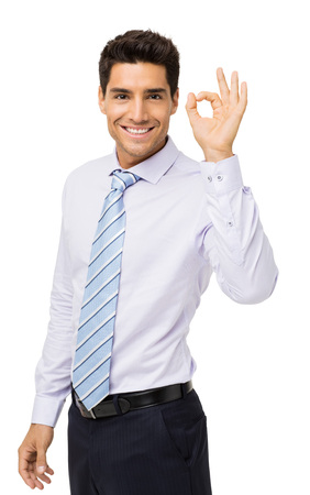 Portrait of confident businessman gesturing okay against white background. Vertical shot. Stock Photo