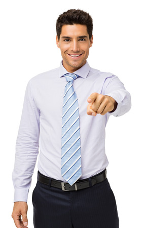 Portrait of smiling young businessman pointing at you against white background. Vertical shot. photo