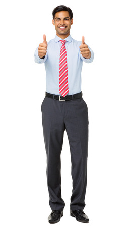Full length portrait of smiling young businessman showing thumbs up against white background. Vertical shot.