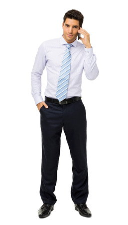 Full length portrait of confident young businessman answering smart phone against white background. Vertical shot.