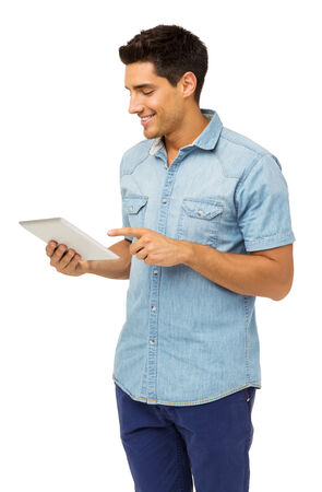 Smiling young man using tablet computer against white background. Vertical shot. photo