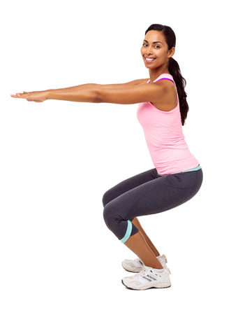 Side view portrait of confident young woman exercising and doing squats against white background. Vertical shot.