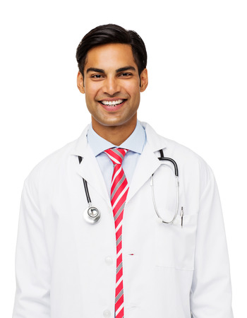 Portrait of confident young male doctor standing against white background. Vertical shot. photo