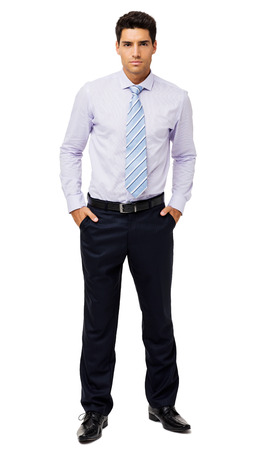 Full length portrait of confident businessman with hands in pockets standing over white background. Vertical shot.