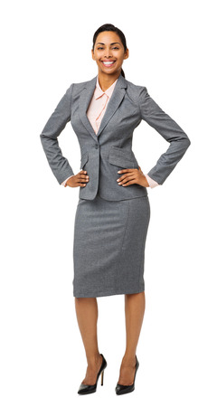 Full length portrait of smiling well-dressed businesswoman standing with hands on hips isolated over white background. Vertical shot. photo