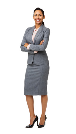 Full length portrait of smiling businesswoman standing arms crossed isolated over white background. Vertical shot. photo