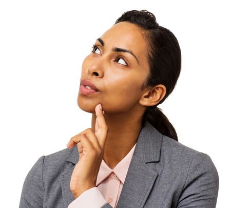 Thoughtful young businesswoman with finger on chin looking up against white background. Horizontal shot. Stock Photo