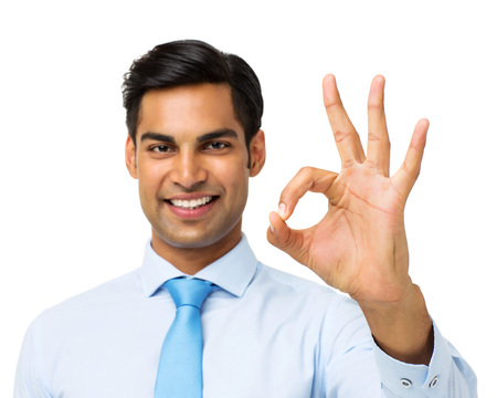 Portrait of happy businessman gesturing okay against white background. Horizontal shot. photo