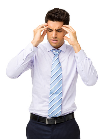 Young businessman suffering from headache standing isolated over white background. Vertical shot. photo
