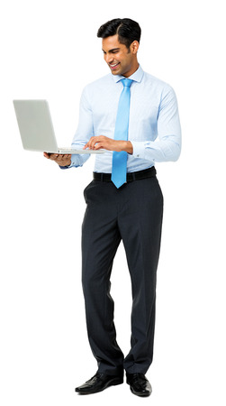 Full length of young businessman using laptop against white background. Vertical shot. Stock Photo