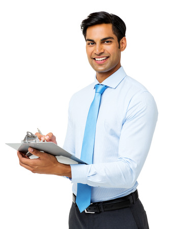 Portrait of confident businessman writing on clipboard against white background. Vertical shot. photo