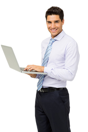 Portrait of confident young businessman with laptop standing against white background. Vertical shot. Stock Photo