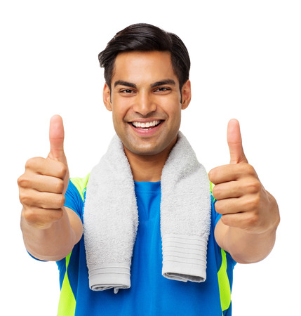 Portrait of confident fit man gesturing thumbs up against white background. Horizontal shot.