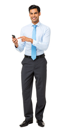 Full length portrait of confident businessman using smart phone isolated over white background. Vertical shot.