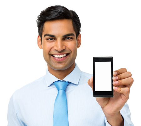 Portrait of confident Indian businessman showing smart phone against white background. Horizontal shot.