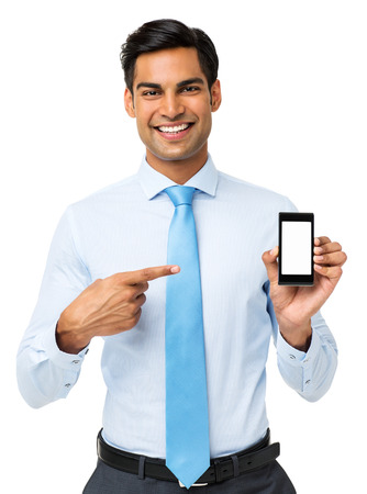 Portrait of smiling businessman pointing at smart phone isolated over white background. Vertical shot.