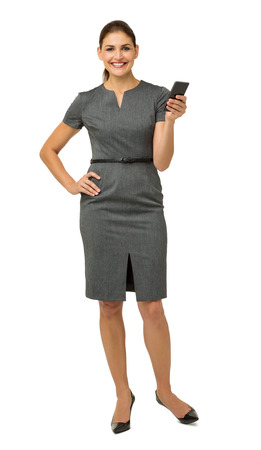 Full length portrait of businesswoman holding smart phone against white background. Vertical shot. photo