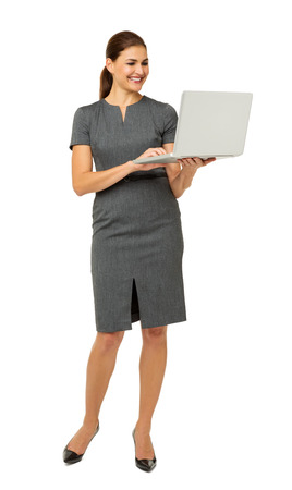 Full length of businesswoman using laptop isolated over white background. Vertical shot. photo