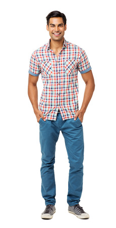 Full length portrait of smiling young man standing with hands in pockets against white background. Vertical shot. Stock Photo