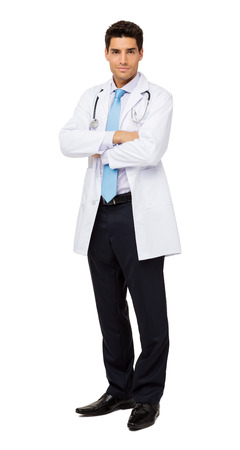 Full length portrait of male doctor standing arms crossed against white background. Vertical shot. photo