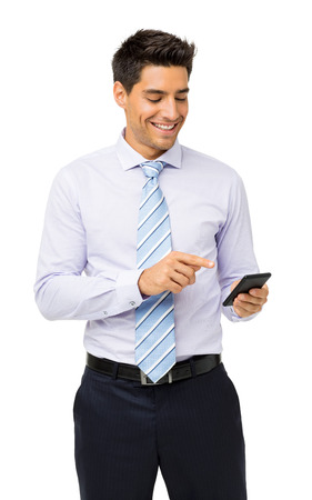 Smiling businessman reading text message on smart phone against white background. Vertical shot.