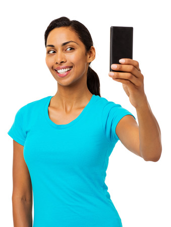 Beautiful young woman taking selfie through smart phone against white background. Vertical shot. photo