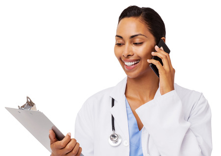 Smiling female doctor reading clipboard while using smart phone over white background. Horizontal shot. photo