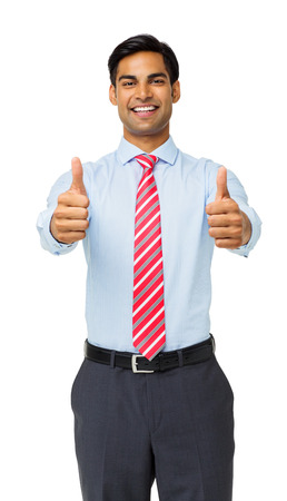 Portrait of confident young businessman gesturing thumbs up while standing against white background. Vertical shot. photo