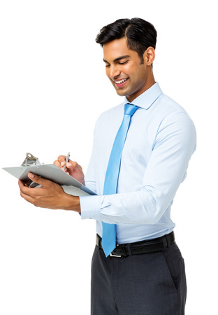 Happy young businessman writing on clipboard while standing against white background. Vertical shot. photo